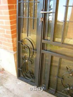 Porte d'entrée en fer forgé plein à 2 battants vitrés poussant à droite