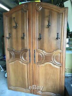 Portes d'armoire anciennes en noyer avec patères faisant office de porte manteau